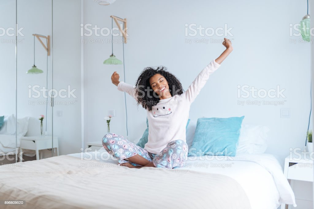 Happy beautiful young black woman relaxed sitting in the bed 'n stock photo