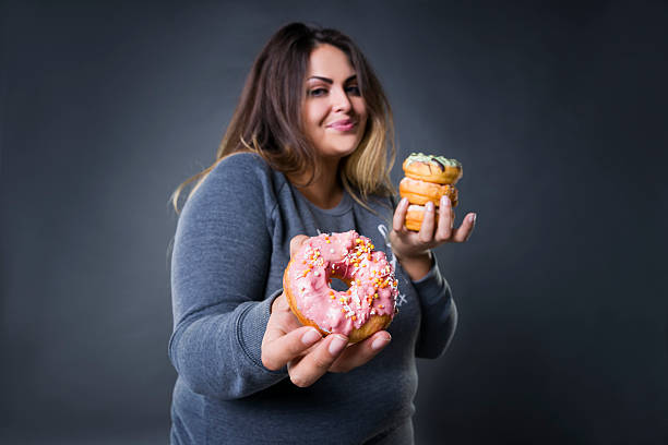 Happy beautiful young caucasian plus size model posing with donuts stock photo