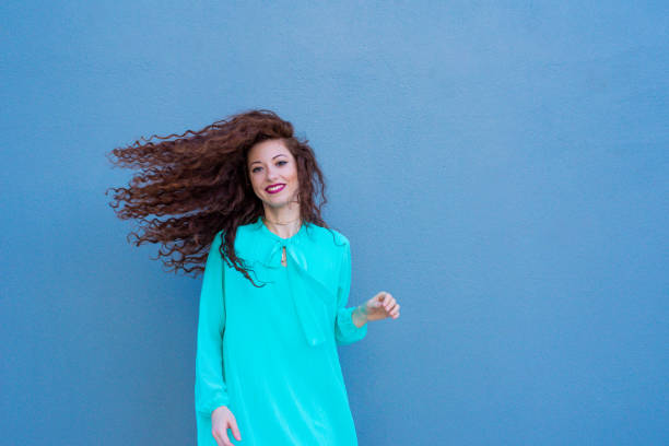 Happy beautiful young redhead woman posing by a colorful wall stock photo