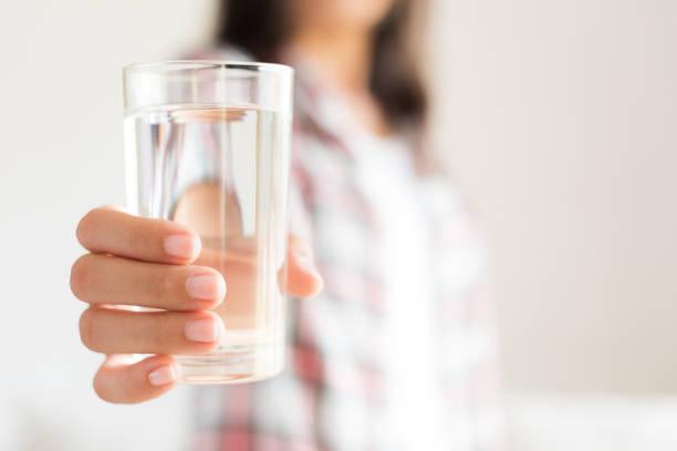 Gerne schöne junge Frau mit Trinkwasser Glas in der Hand. Health care Konzept. – Foto