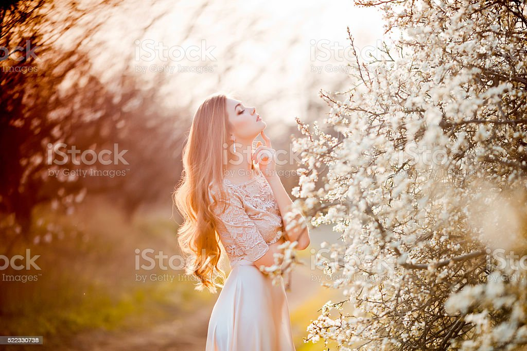 Happy beautiful young woman relaxing in blossom park stock photo