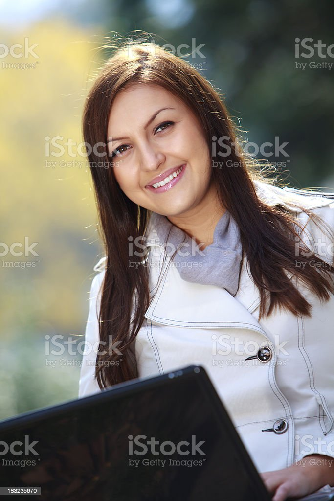 Happy beautiful young woman using laptop in park royalty-free stock photo