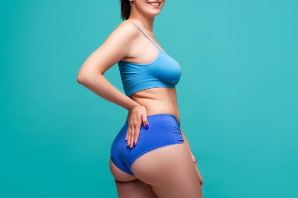 ターコイズ色の背景に大きな胸とトーンのお尻を持つ青い下着で幸せな美しさの女性 - real bodies ストックフォトと画像