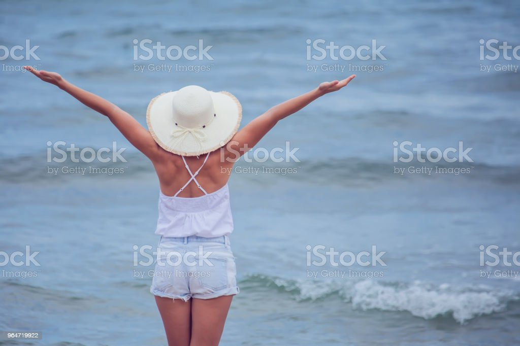 Happy beauty woman in hat is back opened his hands, relaxes and enjoys royalty-free stock photo