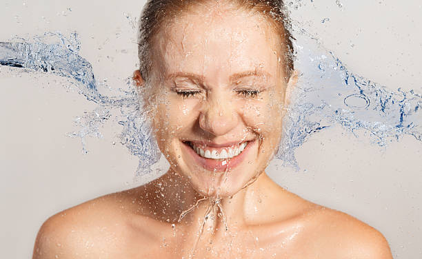 Happy beauty woman skin care, washing with splashes of water stock photo
