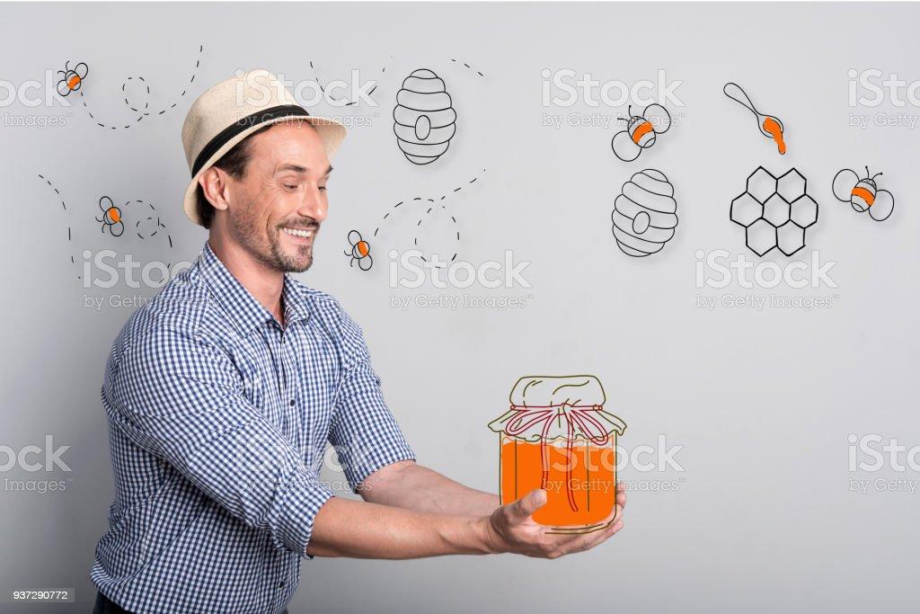 Apiculteur heureux sentais excité tout en tenant un pot de miel - Photo