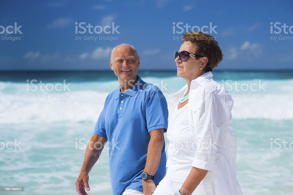 happy best ager couple walking along beach royalty-free stock photo