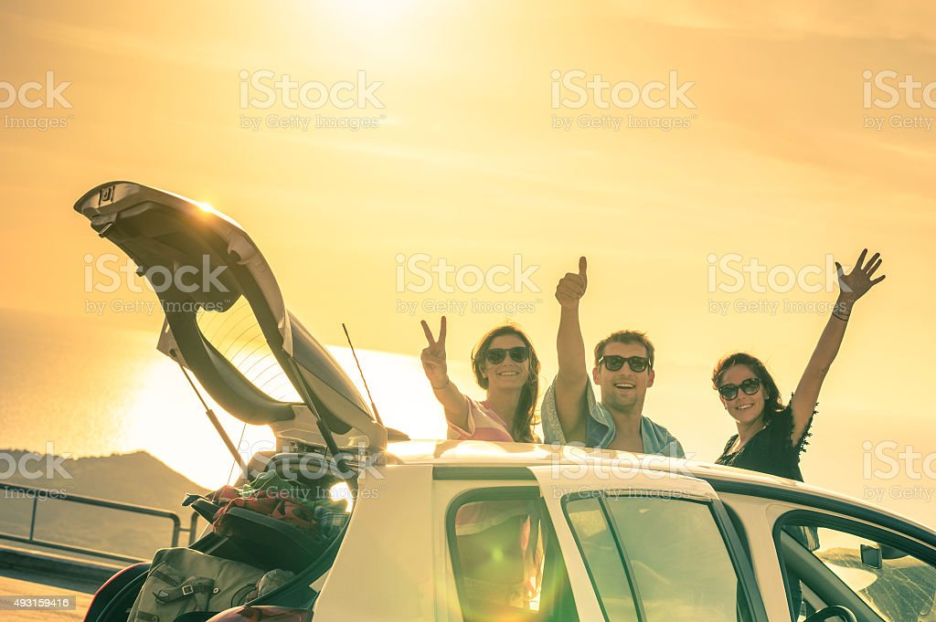 Happy best friends cheering by car road trip at sunset stock photo