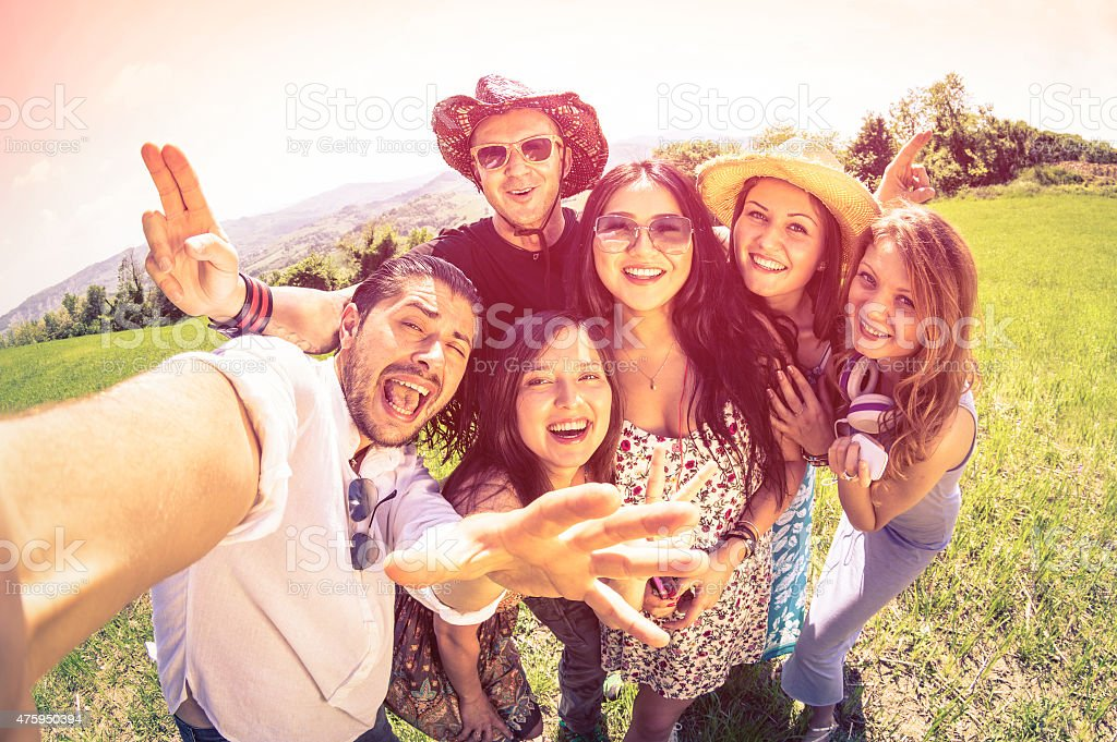 Happy best friends using selfie stick at countryside picnic - Royalty-free 2015 Stock Photo