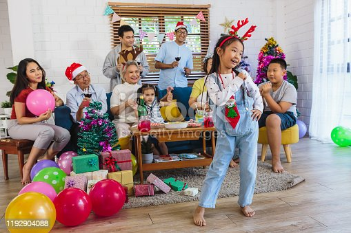 Happy big Asian family enjoy dancing and celebrate Christmas together in living room at home