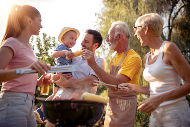 Happy big family gathered around the grill at picnic stock photo
