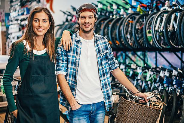 happy bike shop owners - einzelhandelsarbeiter stock-fotos und bilder