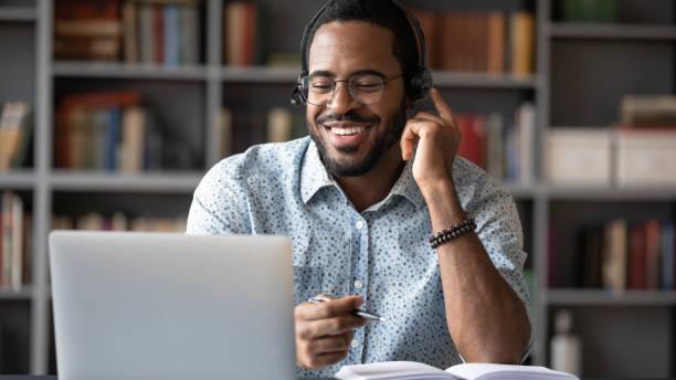 Glücklich biracial männlich in Headset Studium auf modernen Laptop – Foto