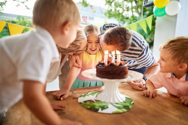 Happy birthday baby Shot of a beautiful family celebrating daughter's birthday, parents kissing her with brothers standing by birthday wishes for daughter stock pictures, royalty-free photos & images