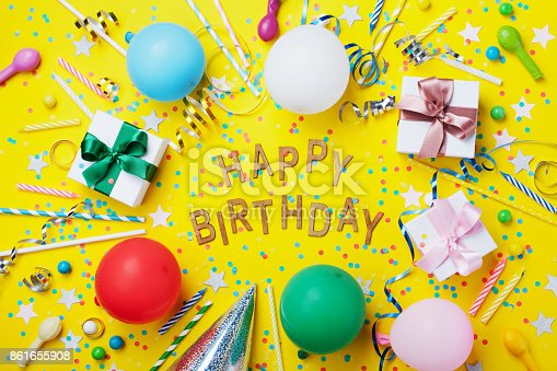 istock Happy birthday background or greeting flyer. Colorful holiday supplies on yellow table top view. Flat lay style. 861655908