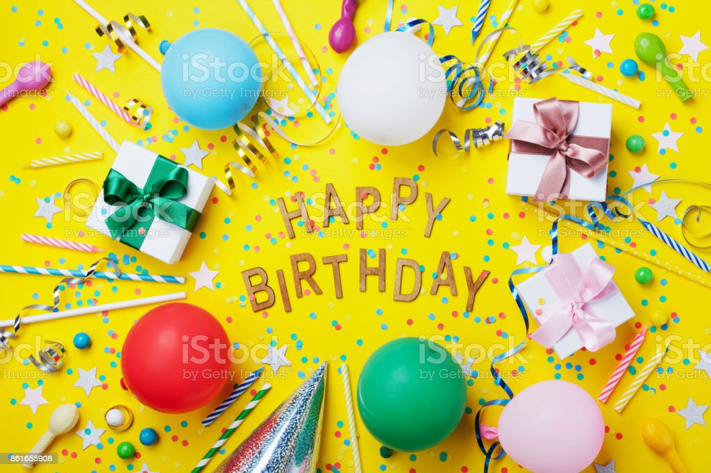 Happy birthday background or greeting flyer. Colorful holiday supplies on yellow table top view. Flat lay style. stock photo