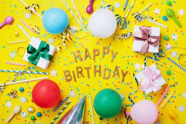 Happy birthday background or greeting flyer. Colorful holiday supplies on yellow table top view. Flat lay style. - foto stock