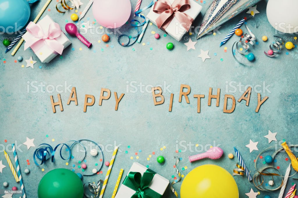 Happy birthday banner. Colorful holiday supplies on blue vintage table top view. Flat lay. stock photo