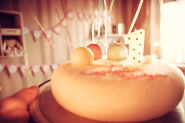 geburtstagstorte für kinderparty mit einer kerze und süße ballons zu ehren des ersten geburtstages als happy birthday hintergrund dekoriert - einladungskarten kindergeburtstag stock-fotos und bilder