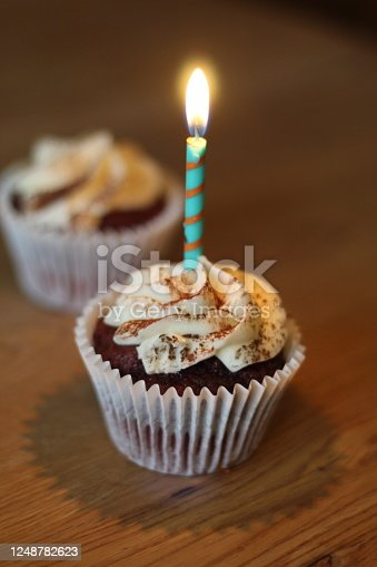 Two chocolate cupcakes, the closed one having just one single candle in it.
