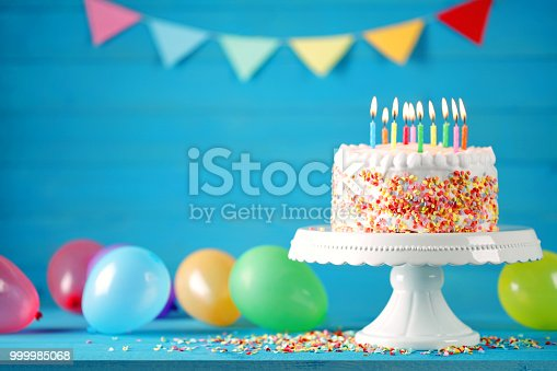 istock Happy birthday cake with burning candles, balloons and pennant 999985068