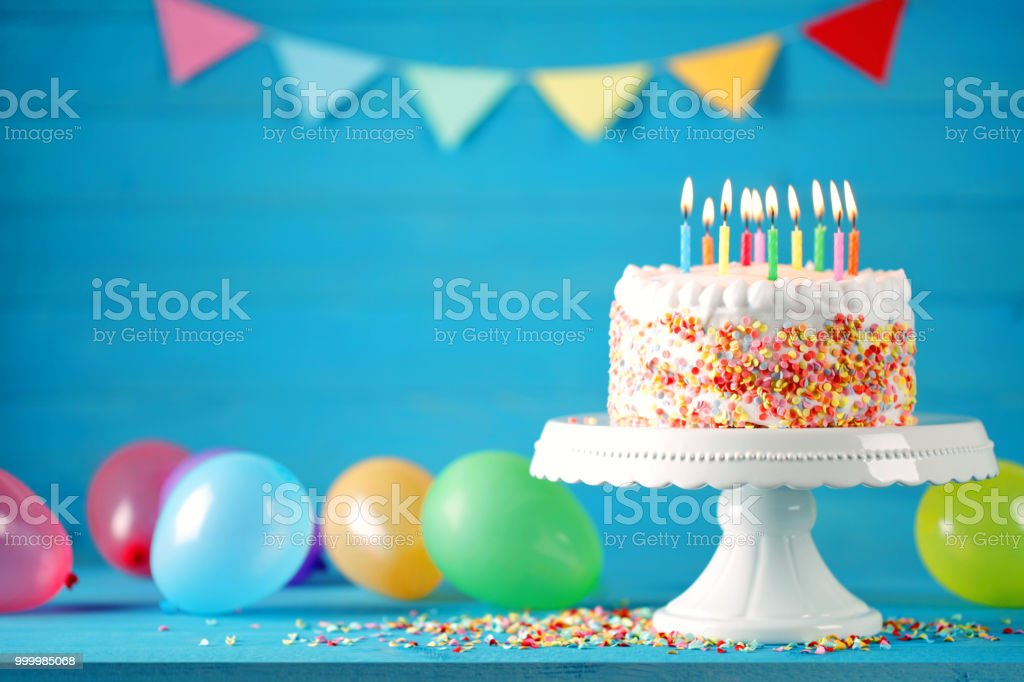 Happy birthday cake with burning candles, balloons and pennant stock photo