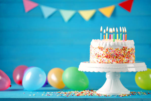 happy birthday cake with burning candles, balloons and pennant - anniversary stock photos and pictures
