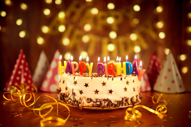 Happy birthday cake with candles on the background of garlands a stock photo
