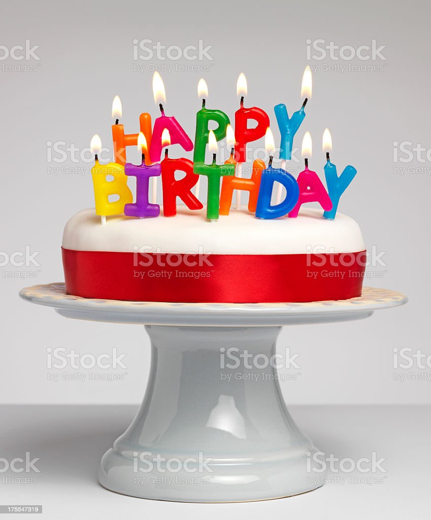 Happy Birthday Candles Lit On White Cake With Red Ribbon Stock Photo