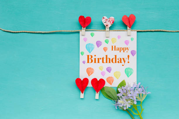 Happy birthday card with red heart clip and purple flower stock photo