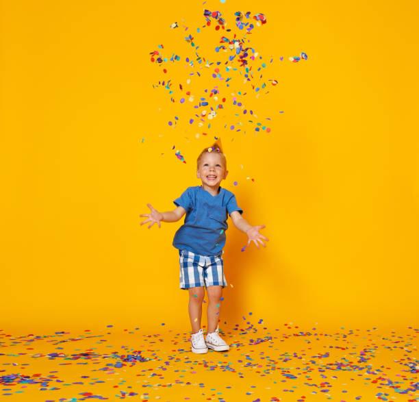 Glücklicher Geburtstagskind mit Konfetti auf gelbem Hintergrund – Foto