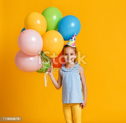 happy Birthday! child girl with balloons on yellow color background