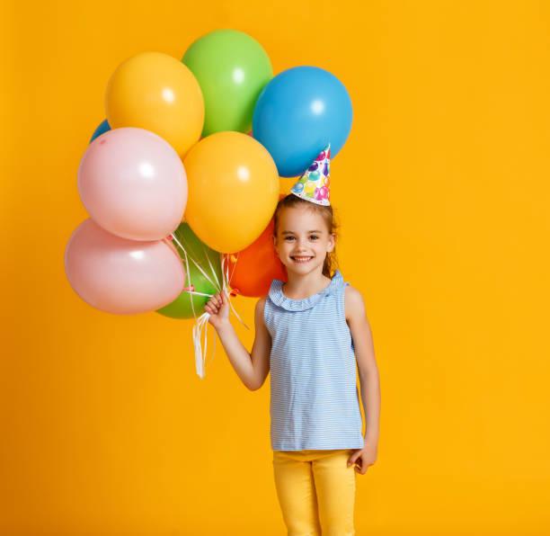 Herzlichen Glückwunsch zum Geburtstag! Kind Mädchen mit Luftballons auf gelbem Hintergrund – Foto