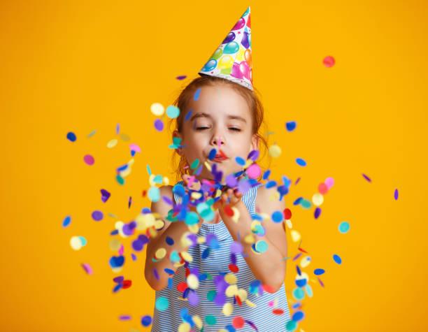 alles Gute zum Geburtstag Kind Mädchen mit Konfetti auf gelbem Hintergrund – Foto