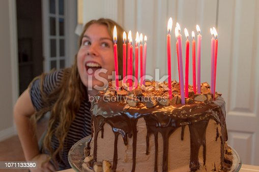 This teenage girl is celebrating a recent birthday with a giant chocolate cake.  Lots of burning candles up there on this happy occasion.
