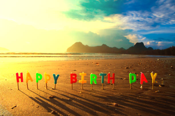 Happy birthday colorful candles on a beach sunrise.