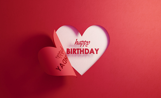 Happy birthday text is inside of a red folding heart shape on white background. Horizontal composition with  copy space.