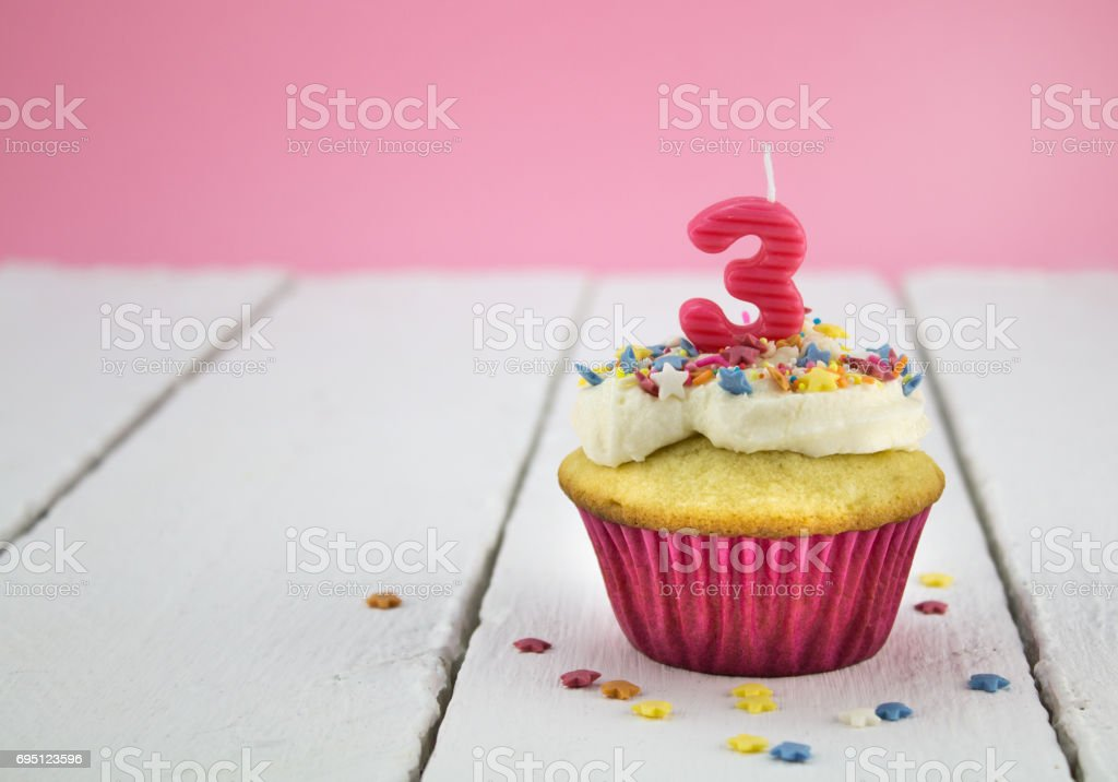 Happy Birthday Cup Cake With Star Sprinkles And Number 3 Pink Candle On White Tabel