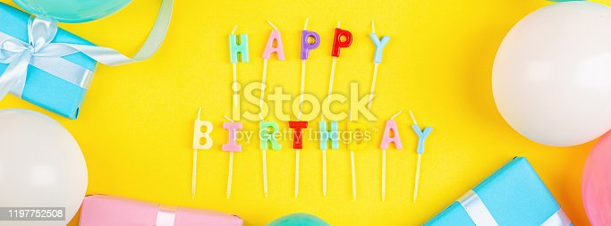 1093222958 istock photo Happy birthday greeting text maked with candles and decorated with confetti on yellow background, top view. Flat lay style. Mockup, template 1197752508