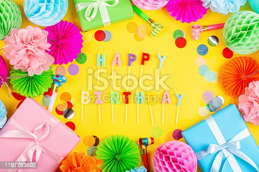 1093222958 istock photo Happy birthday greeting text maked with candles and decorated with confetti on yellow background, top view. Flat lay style. Mockup, template 1197753602