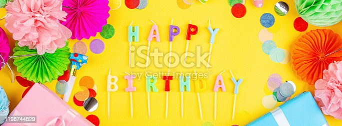 1093222958 istock photo Happy birthday greeting text maked with candles and decorated with confetti on yellow background, top view. Flat lay style. Mockup, template 1198744829