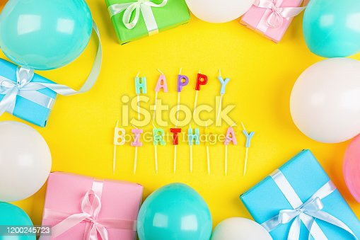 1093222958 istock photo Happy birthday greeting text maked with candles and decorated with confetti on yellow background, top view. Flat lay style. Mockup, template 1200245723