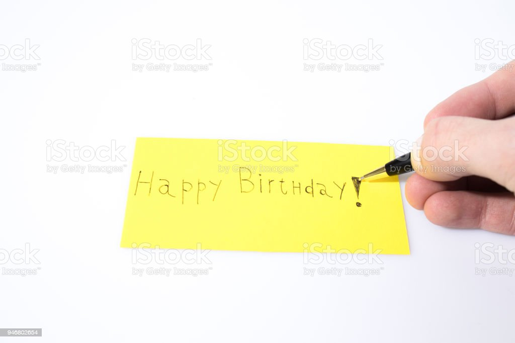 Happy birthday handwrite with a pen and a hand on a yellow paper composition stock photo