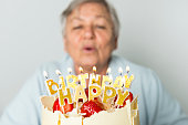 Senior woman with birthday cake on gray background.
