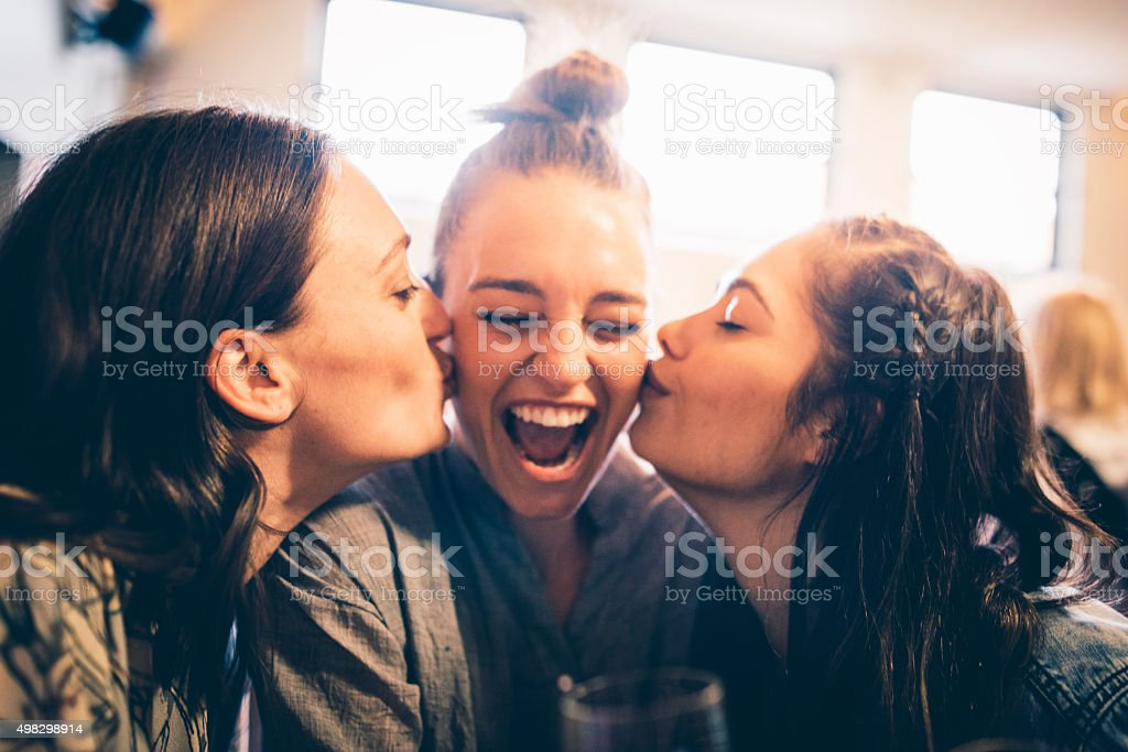 Three young women in a bar. Two of them are kissing the third one for...