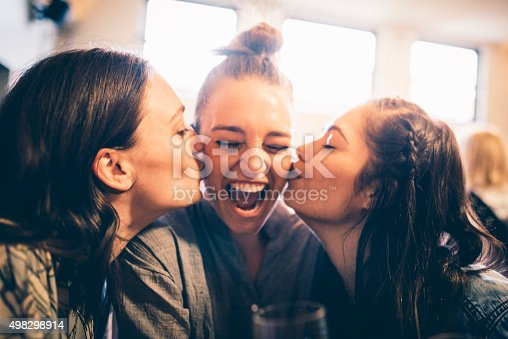 Three young women in a bar. Two of them are kissing the third one for her birthday. They are having fun.