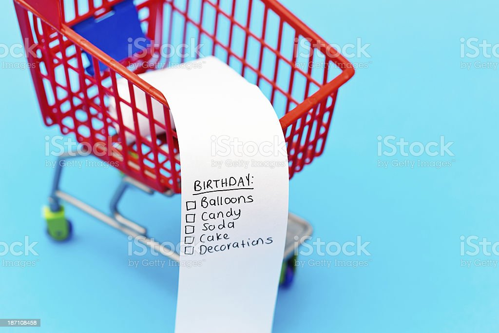 A miniature shopping cart contains a shopping list headed Birthday...