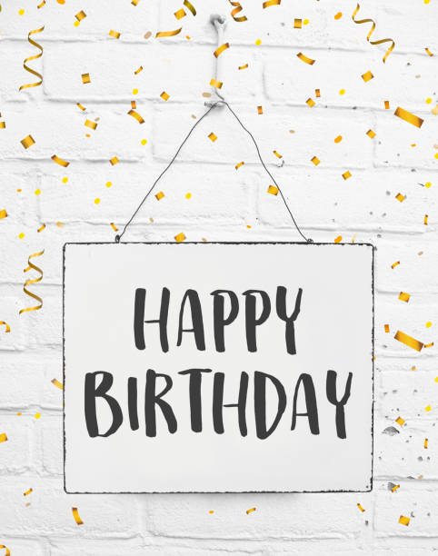 Happy birthday text. Banner on white brick background with golden party confetti stock photo