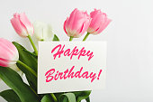 Happy Birthday text on gift card in flower bouquet. Beautiful bouquet of fresh flowers tulips with greeting card Happy Birthday on white background