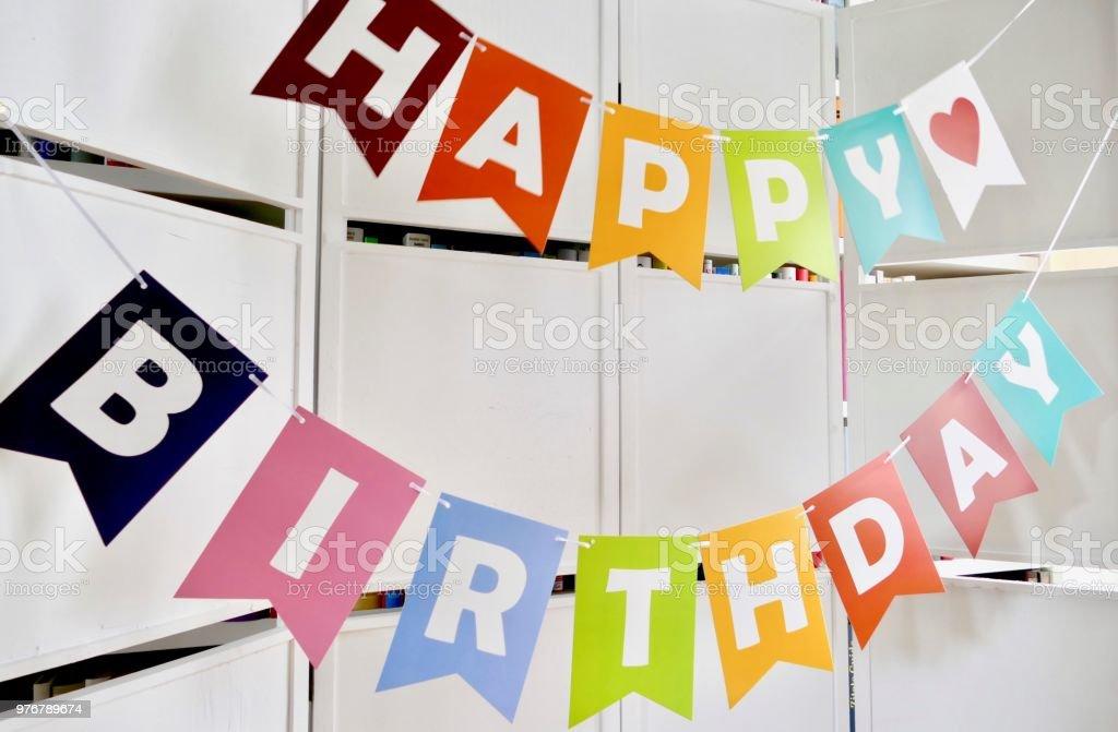 Happy birthday text on  white wooden wall stock photo